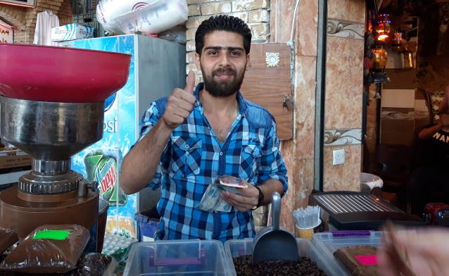 Irakilainen yrittäjä näyttää peukaloa ylöspäin.
